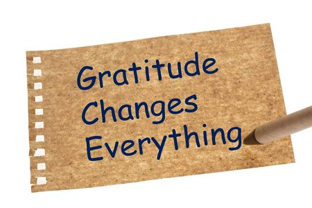 Gratitude Changes Everything on recycled paper sheet and recycled paper pen.