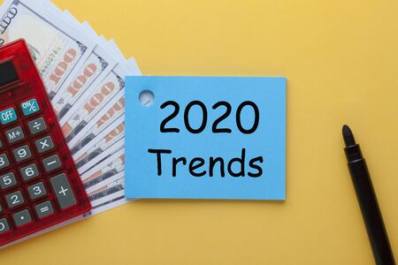 2020 Trends written on note with marker, calculator and dollars. Business Concept.