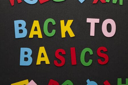 Back to basics text spelled with colorful alphabet letters on black background.