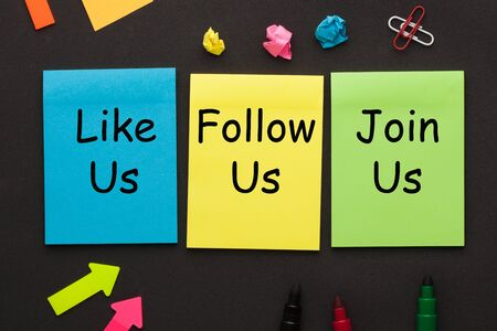 Like Us, Follow Us and Join Us text on color notes and office supplies on black background. Concept of social media marketing and management.