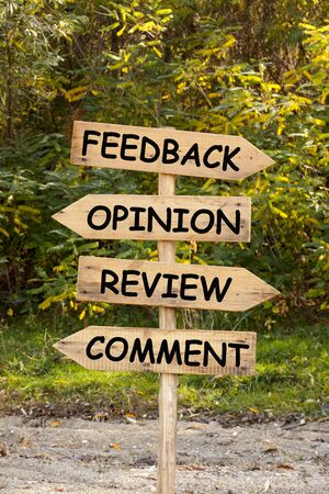 The words Feedback, Opinion, Review and Comment on wooden direction arrow road sign with forest background.