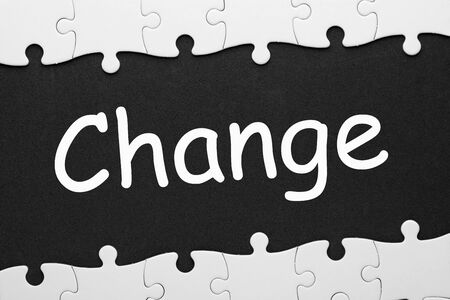 Change sign and puzzle pieces over black surface. Фото со стока