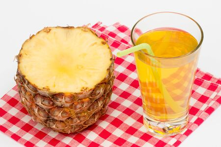 Glass of pineapple juice and pineapple on the tablecloth Фото со стока