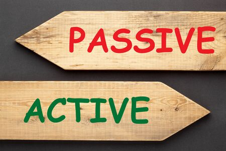 The words Passive and Active written on old wooden arrows on black background.