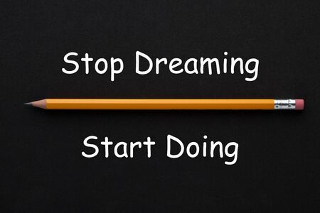 The words Stop Dreaming Start Doing with pencil on black background. Motivational quote. Фото со стока