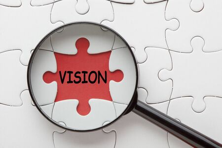 The word Vision with magnifying glass over jigsaw puzzle.