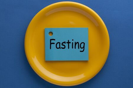 The word Fasting in sticky note on plate. How to start Фото со стока