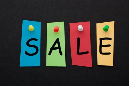 The word sale written in colorful stickers pinned on black background. Business concept Фото со стока