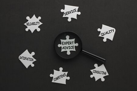 Expert Advice diagram with magnifying glass and conceptual words on white puzzle pieces. Business concept.