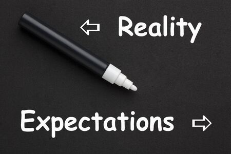 The words Reality and Expectations written with white marker on black background.