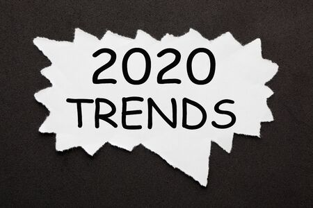 2020 Trends text on torn piece of paper over black surface. Фото со стока