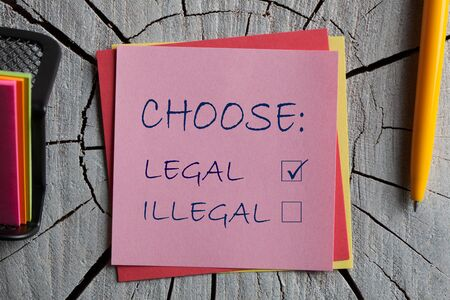 Choose Legal and illegal on note with pen on wooden surface.