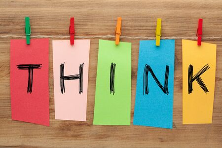 The word Think written on set stickers with clip hanging on a rope on wooden background.
