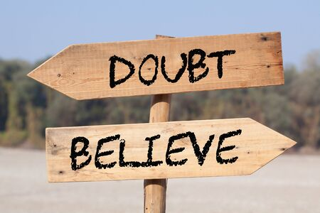 Belief Vs Doubt on wooden road sign with left and right arrows.