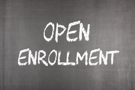 Open enrollment written on blackboard. Health concept Фото со стока