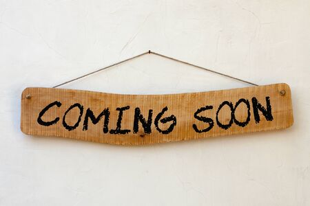 Wooden sign hanging on a rope on white background with text: Coming Soon. Business concept.