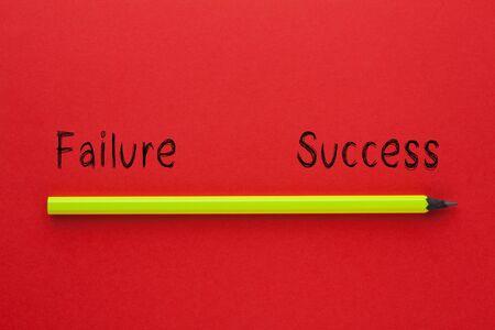 Die Worte Erfolg gegen Misserfolg und Bleistift auf rotem Hintergrund. Unternehmenskonzept.