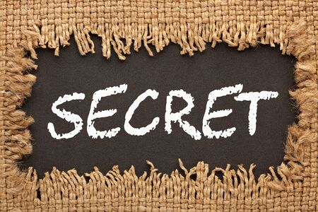 Piece of burlap with hole with the word Secret. Business concept Фото со стока
