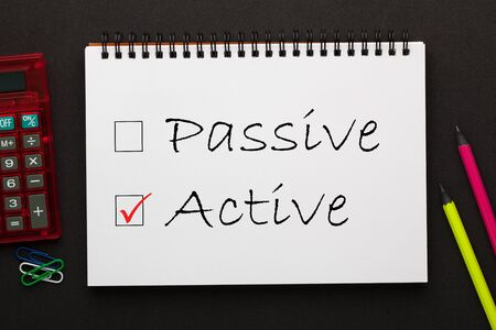 Passive or Active words written on notepad with pencil and calculator a side. Business concept.