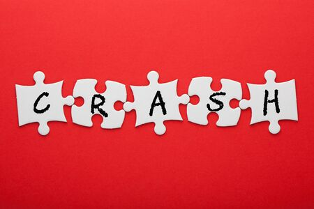 Crash word in pieces paper puzzle on red background. Business concept. Imagens