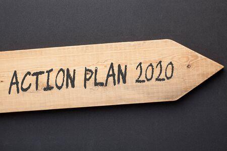Action Plan 2020 written on old wooden arrow on black background.