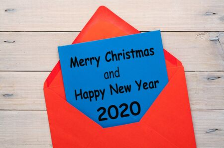 Merry Christmas and Happy New Year 2020 message in red envelope on wooden background. Xmas concept 版權商用圖片