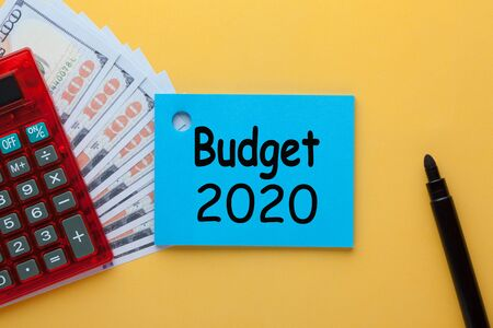 Budget 2020 written on note with marker, calculator and dollars. Business concept.
