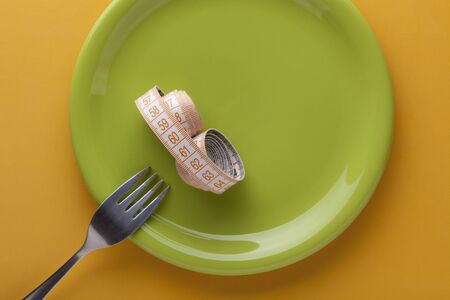 Measuring tape and fork on green plate. Fasting and diet concept Stockfoto