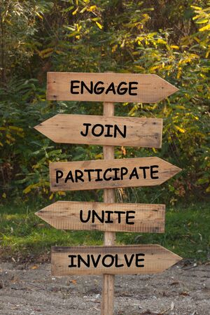 Wooden road sign with words Engage, Join, Participate, Unite and Involve.