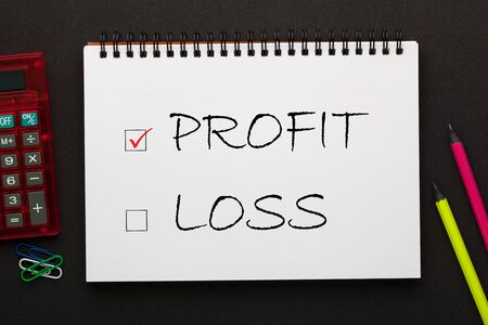 Profit and Loss check boxes written on notepad with pencil and calculator a side. Business concept.