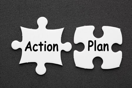The words Action Plan on two matching puzzle on black background. Business concept Stock Photo