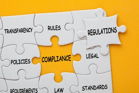 Missing jigsaw puzzle piece with text regulations, covering text project and different business words which matches a yellow space marked compliance. Stock Photo