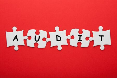 Audit word in pieces paper puzzle on red background. Business concept.