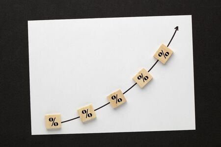 Percentage symbol with directional arrow written on cubes shape wooden blocks. Interest rate concept
