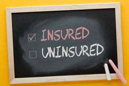 Insured checked and uninsured written on blackboard and color chalks. Stockfoto