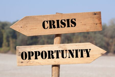 Crisis or opportunity words on wooden road sign with left and right arrows. Stockfoto
