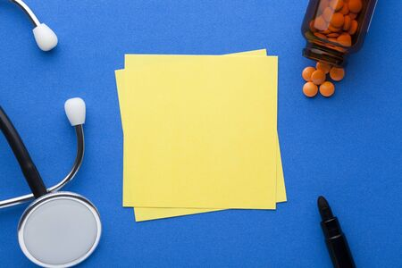 Blank yellow note with stethoscope, pills and various stationery on blue background with space for text. Medical concept Stockfoto