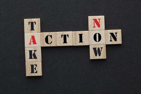 Take action now concept crossword in wooden blocks on black background. Stockfoto