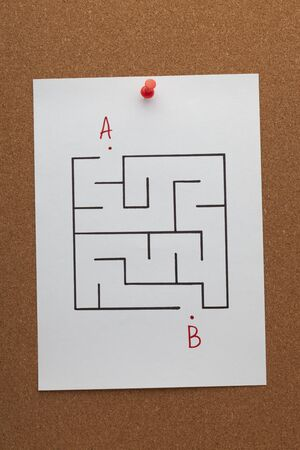 Find path in a maze concept on white paper sheet pinned on cork board.
