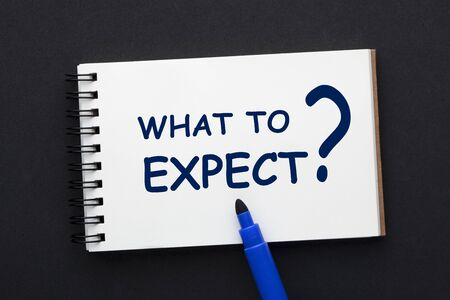 What to expect text on notepad with blue marker on black background.