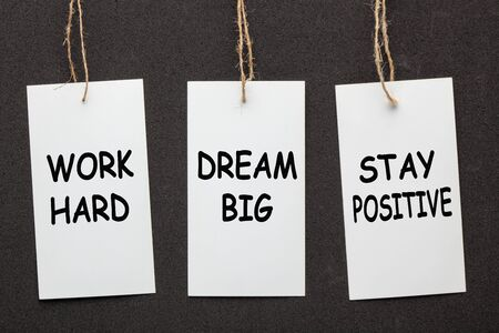 Work hard, dream big and stay positive written on paper labels set on black background.