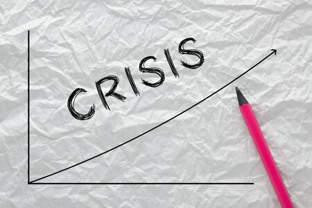 The word crisis with directional arrow written with pencil on wrinkled lined paper.  Stockfoto
