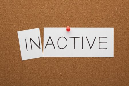 Changing word inactive transformed to active on a white sheet pinned on cork board.  Stockfoto