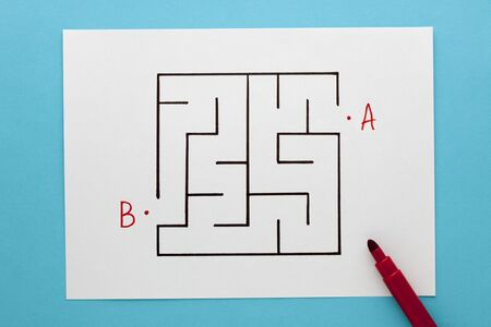 Find path in a maze concept on white paper sheet on blue background Stock Photo