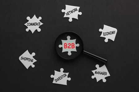 Business-to-business diagram with magnifying glass on white puzzle pieces. Business concept.