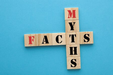 Facts and myths in wooden blocks on blue background. Concept crossword clues Stockfoto