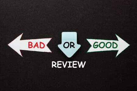 Review: bad or good? text and paper arrows on black background. Business concept.