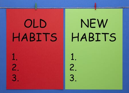 Old Habits and New Habits written on color paper sheets with wooden pinch on blue background.