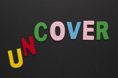 Words uncover transformed to cover made of colorful alphabet letters on black background.
