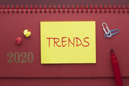 2020 Trends written on note with marker on red background. Business Concept.